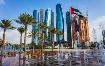 Dubai sky scrapers with flag and water fountain